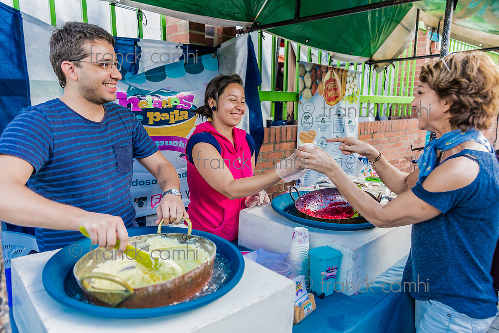 Bogota, Colombia  - February 6, 2017 : woman eating helados de pailla ice scream tradiotional street food at Mercado de las Pulgas de Usaquen free market  in Bogota capital city of Colombia South America
