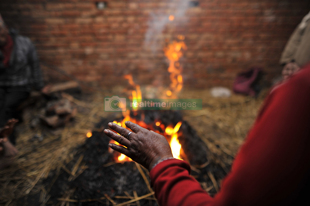 January 31, 2018 - Kathmandu, Nepal - Nepalese Hindu devotee warm themselves after taking a holy bath during Last Day of Madhav Narayan Festival or Swasthani Brata Katha festival at Hanumante River, Bhaktapur, Nepal on Wednesday, January 31, 2018. Nepalese Hindu women observe a fast and pray to Goddess Swasthani for Long life of their husbands and family prosperity during a month-long fasting festival celebration. (Credit Image: © Narayan Maharjan/NurPhoto via ZUMA Press)