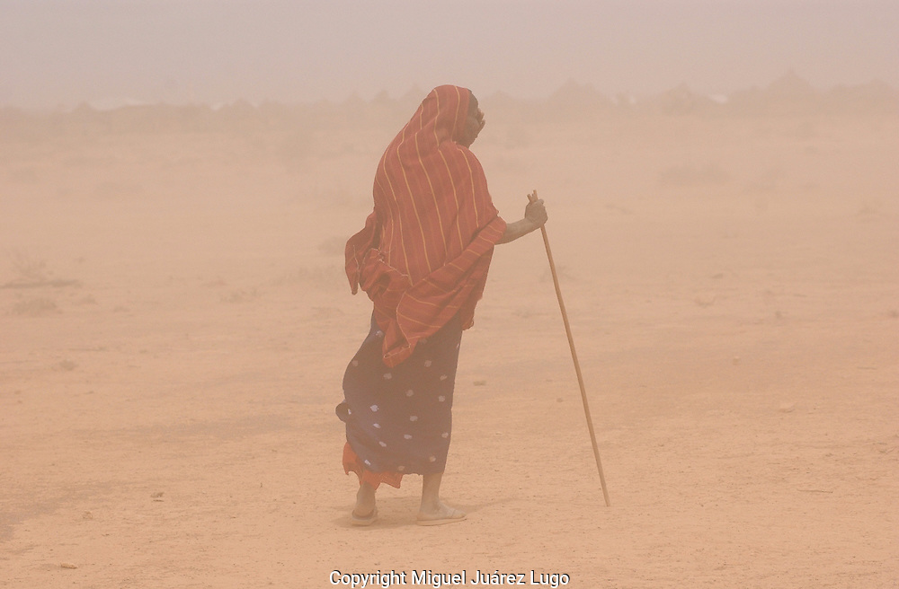 El Barde, Somalia.   A woman walks in a sand storm in search of  people collecting  their monthly food ration in a distribution center run by the World Food Programme in El Barde, Somalia.  This region of northern Somalia, close to the Ethiopia's border has been suffering  years of a severe drought.  (PHOTO: MIGUEL JUAREZ LUGO)