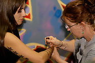Lily Whitehead of Dayton (right) applies Henna art during LadyFest 2010 at c{space in downtown Dayton, Saturday, September 4, 2010.