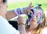 Brianna Chambers (right), 8 has her face painted by Judy Dabrow (left) during the annual first Fourth event at Newtown Middle School Saturday July 11, 2015 in Newtown, Pennsylvania. The celebration was held a week late this year cause fireworks company couldn't make it on July 4th. (Photo by William Thomas Cain)