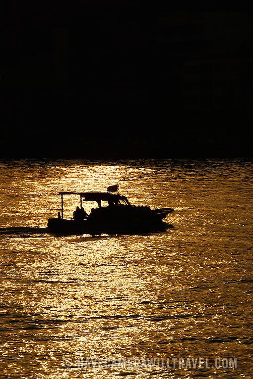 A small fishing boat is silhouetted against the glistening water of the Bosphorus during a golden sunset in Istanbul, Turkey.