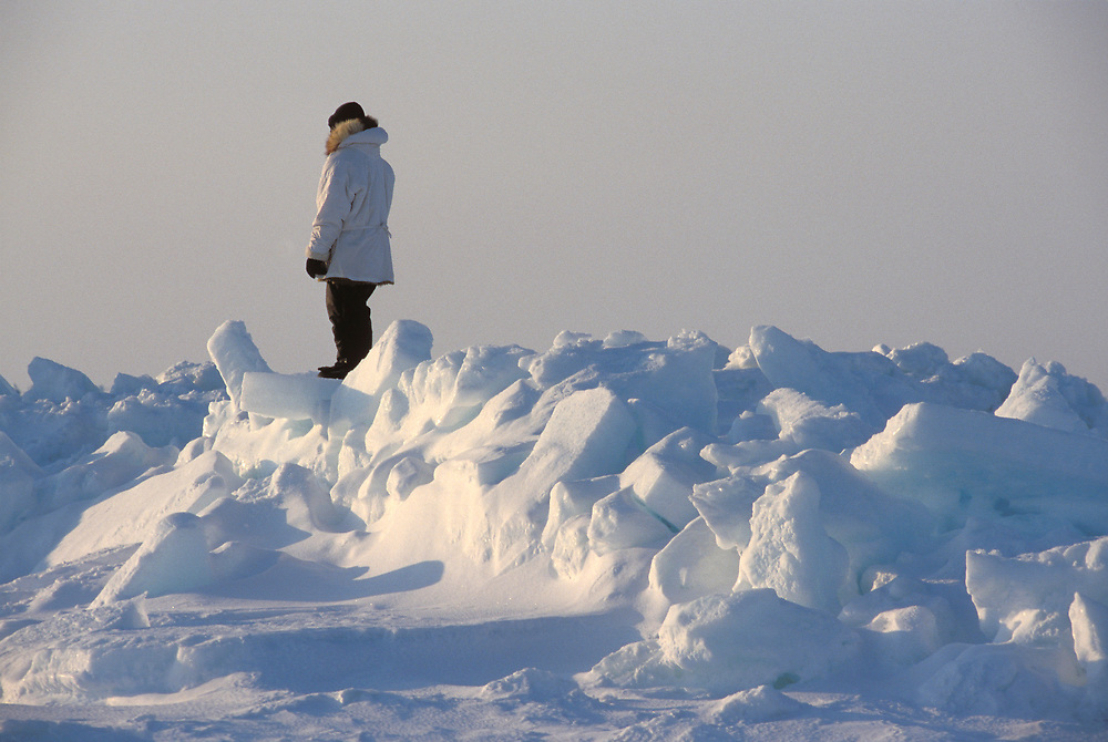 Native Alaskan whalers in parkas standing on boulders of ice to get a good view over the Chukchi Sea and spot bowhead whales that are close enough to shore to hunt