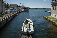 A boater coming out from under the bridge at the Back Bay heading out to Lake Winnipesaukee in Wolfeboro, NH.  (Karen Bobotas/Photographer)