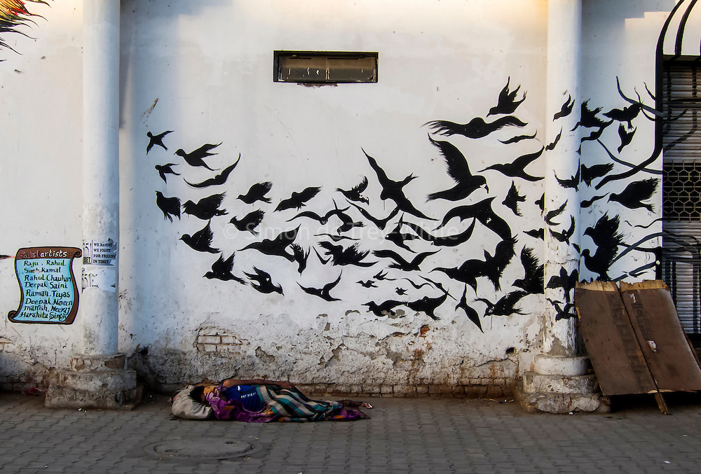 13th April 2016, New Delhi. A man sleeps in front of a wall-mural in New Delhi, India on the 13th April 2016<br /> <br /> Sleeping in the outdoors is common in Asia due to a warmer climate and the fact that personal privacy for sleep is not so culturally ingrained as it is in the West. New Delhi (where most of these images were taken) is a harsh city both in climate and environment and for those working long hours, often in hard manual labour, sleep and rest is something fallen into when exhaustion overwhelms, no matter the place or circumstance. Then there are the homeless, in Delhi figures for them from Government and NGO sources vary wildly from 25,000 to more than 10 times that. Others public sleepers may simply be travellers having a siesta along the way.<br /> <br /> PHOTOGRAPH BY AND COPYRIGHT OF SIMON DE TREY-WHITE, photographer in Delhi<br /> <br /> + 91 98103 99809<br /> email: simon@simondetreywhite.com