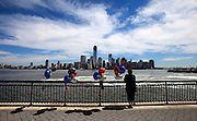 People visit the Jersey City 9/11 Memorial and leave mementoes along the waterfront, where the Freedom Tower, which is being built on the World Center site, rises from the skyline on 9/11/12.