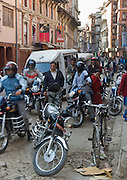 Motorcycles, cars, bicycles, and pedestrians crowd the narrow streets of Kathmandu, Nepal, Asia.