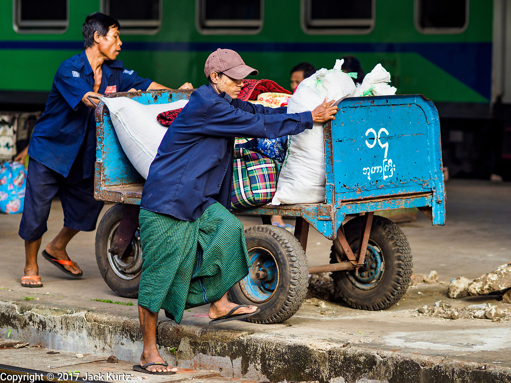 25 NOVEMBER 2017 - YANGON, MYANMAR: Porters carry luggage to a train in the Yangon Central Railroad Station. The Yangon Circular Train is a 45.9-kilometre (28.5 mi) 39-station two track loop system connects satellite towns and suburban areas to downtown. The train was built during the British colonial period, the second track was built in 1954. Trains currently run both directions (clockwise and counter-clockwise) around the city. The trains are the least expensive way to get across Yangon and they are very popular with Yangon's working class. About 100,000 people ride the train every day. A a ticket costs 200 Kyat (about .17¢ US) for the entire 28.5 mile loop.    PHOTO BY JACK KURTZ