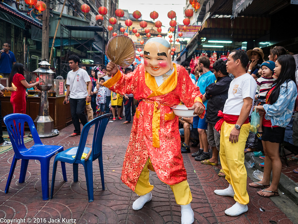 """08 FEBRUARY 2016 - BANGKOK, THAILAND:  A member of a lion dance troupe performs for Chinese New Year at a small Chinese shrine in Bangkok's Chinatown district, during the celebration of the Lunar New Year. Chinese New Year is also called Lunar New Year or Tet (in Vietnamese communities). This year is the """"Year of the Monkey."""" Thailand has the largest overseas Chinese population in the world; about 14 percent of Thais are of Chinese ancestry and some Chinese holidays, especially Chinese New Year, are widely celebrated in Thailand.      PHOTO BY JACK KURTZ"""