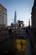 With the Shard in the background, a female pedestrian looks unsure about her safety in the tunnel under London Bridge during the evening rush-hour, on 8th November 2018, in London, England.