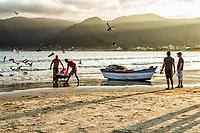 Pescadores ao lado de barco de pesca sobre a areia na Praia do Pântano do Sul. Florianópolis, Santa Catarina, Brasil. / Fishermen and fishing boat on the sand at Pantano do Sul Beach. Florianopolis, Santa Catarina, Brazil.