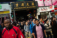 """For a story by Dan Levin slug Hong Kong.February 13 2013, Kowloon, Hong Kong.Pedestrians walking in front of the Chungking Mansions. The Mansions are situated on Nathan Road also called the """"Golden Mile"""", a central street of Hong Kong heavy with traffic and popular with tourists. Stores lining Nathan Road make great business catering to the need of its crowds..Credit: Gilles Sabrie for The New York Times.."""