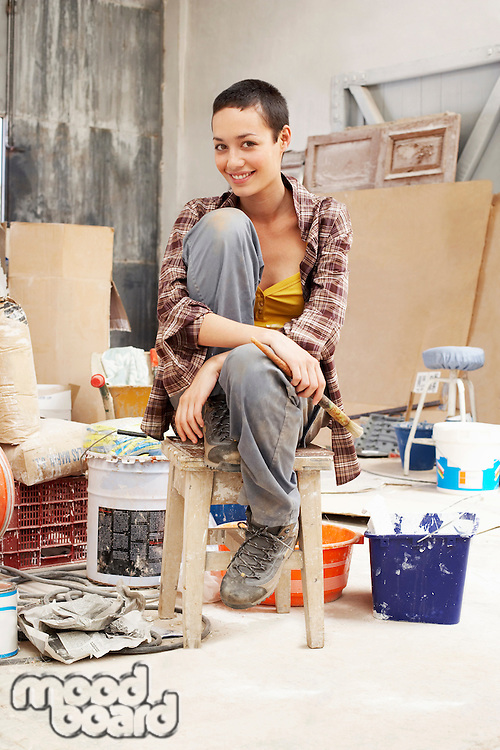 Young female Painter sitting in work site with equipment portrait
