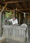 Elodie Michel, ropemaker, at work making a length of rope in the rope makers' workshop at the Chateau de Guedelon, a castle built since 1997 using only medieval materials and processes, photographed in 2017, in Treigny, Yonne, Burgundy, France. The Guedelon project was begun in 1997 by Michel Guyot, owner of the nearby Chateau de Saint-Fargeau, with architect Jacques Moulin. It is an educational and scientific project with the aim of understanding medieval building techniques and the chateau should be completed in the 2020s. Picture by Manuel Cohen