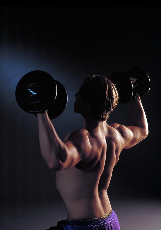 Man doing shoulder presses with dumbbells