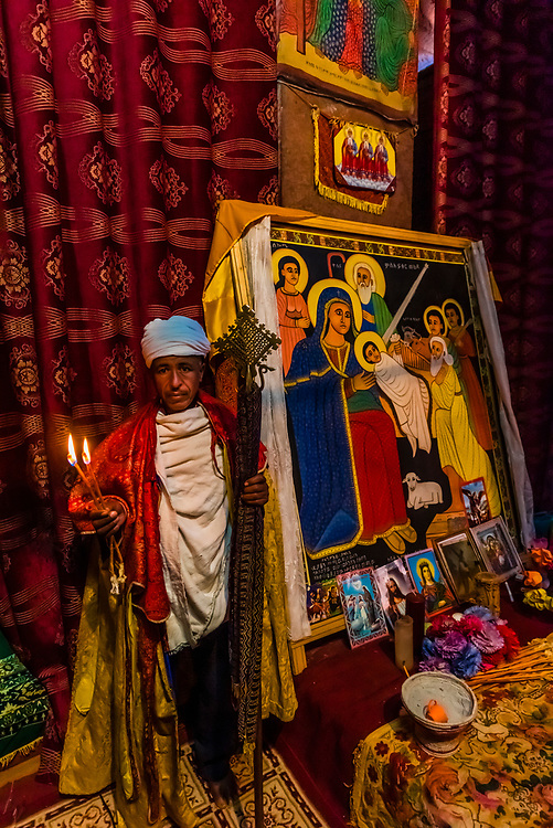 Priest holding honey wax candles, Bet Amanuel, one of 11 rock hewn medieval monolithic churches in Lalibela, Ethiopia.
