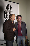 John Varvatos and Nicky Haslam in front of Helmut Newton photograph at thepreview of the forthcoming auction of photographs. Philips de Pury and Luxembourg. 26 September 2002.  of © Copyright Photograph by Dafydd Jones 66 Stockwell Park Rd. London SW9 0DA Tel 020 7733 0108 www.dafjones.com