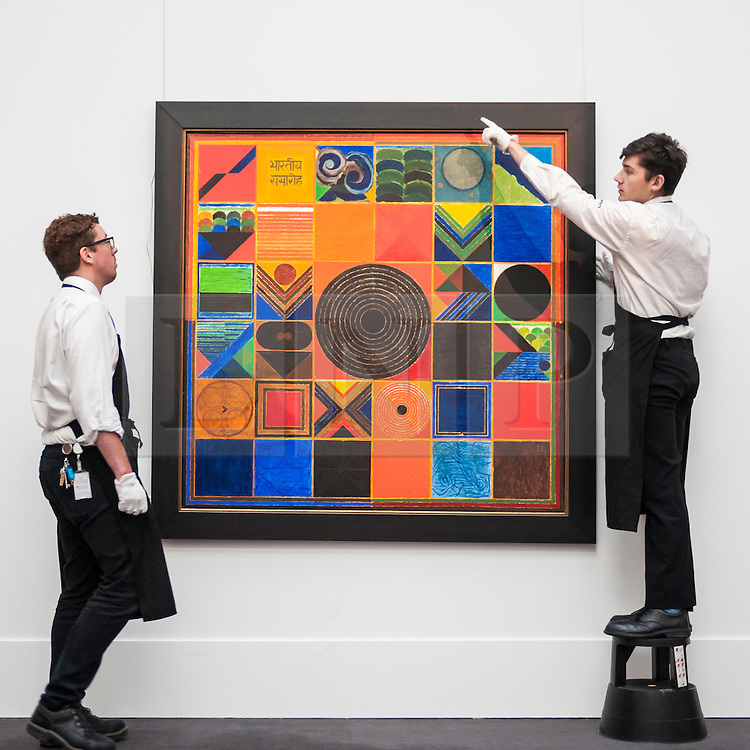 """© Licensed to London News Pictures. 02/10/2015. London, UK. Sotheby's technicians help to hang """"Bhartiya Samaroh"""" by Sayed Haider Raza (est. £500k - 700k) at the preview of Indian and Islamic Art Week at Sotheby's which runs from 2 to 7 October.  Photo credit : Stephen Chung/LNP"""