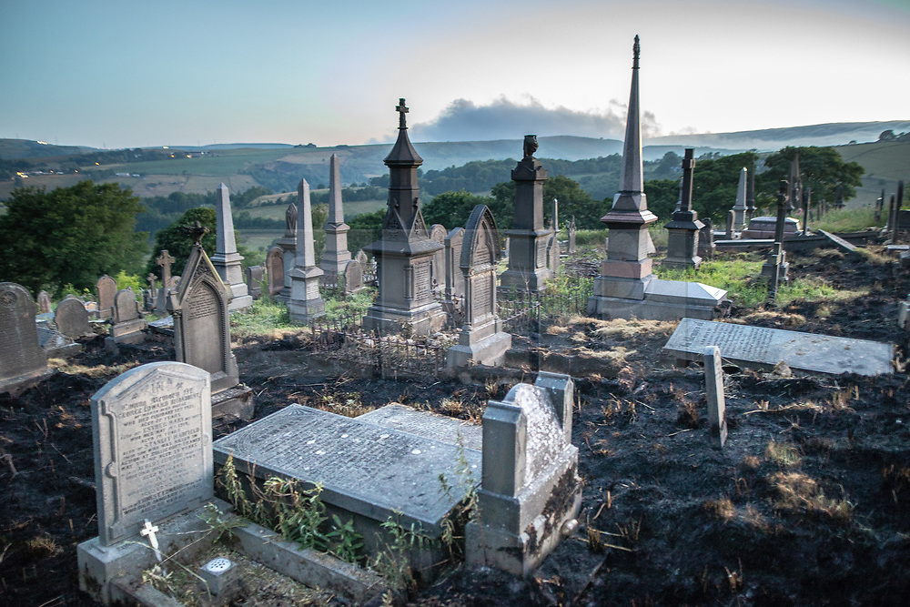 """© Licensed to London News Pictures . 28/06/2018 . Saddleworth , UK . View of smoke on hills across Saddleworth moor across scorched earth in Saddleworth Graveyard , where fire burned through dry grass in the late hours of Wednesday 27th June (yesterday) and had to be extinguished by firefighters . The army are being called in to support fire-fighters , who continue to work to contain large wildfires spreading across Saddleworth Moor and affecting people across Manchester and surrounding towns . Very high temperatures , winds and dry peat are hampering efforts to contain the fire , described as """" unprecedented """" by police and reported to be the largest in living memory . Photo credit: Joel Goodman/LNP"""