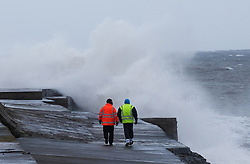 © Licensed to London News Pictures. <br /> 01/02/2015. <br /> <br /> South Gare, Redcar, United Kingdom<br /> <br /> Two men walk along the seawall as huge waves crash against it at South Gare near Redcar in Teesside.<br /> <br /> Photo credit : Ian Forsyth/LNP