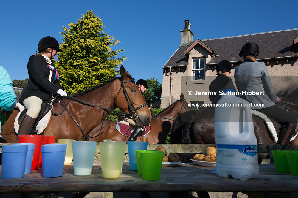 Horsemen, take refreshments of cups of milk, at Linglie Farm, after crossing the River Ettrick, at the start of the Common Riding festivities in Selkirk, with Royal Burgh Standard Bearer Martin Rodgerson, in Selkirk, Scotland, Friday 14th June 2013. <br /> N55&deg;33.438'<br /> W2&deg;50.732'