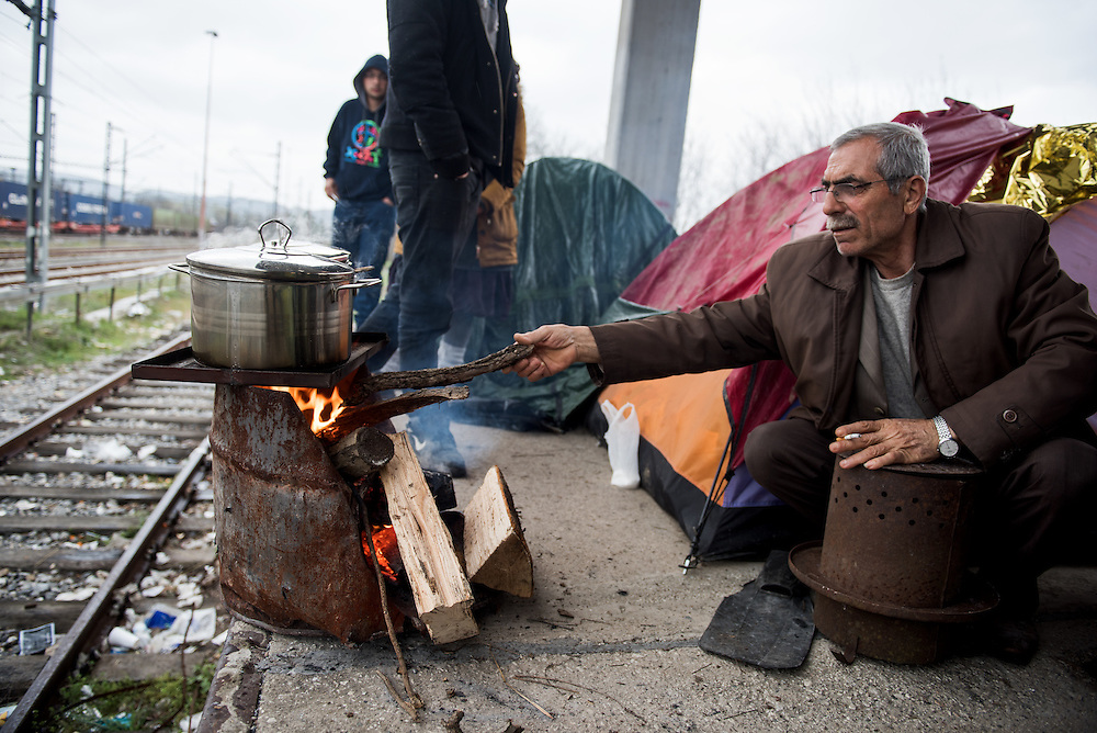 A refugee from Aleppo, Syria is cooking for first time in his life in an open fire at the railway station of Idomeni near the refugee transit camp. <br /> <br /> Thousands of refugees are stranded in Idomeni unable to cross the border. The facilities here are stretched to the limit and the conditions are appalling. It's raining, it's cold there is mud everywhere and there is no hope that the border will open anytime soon.