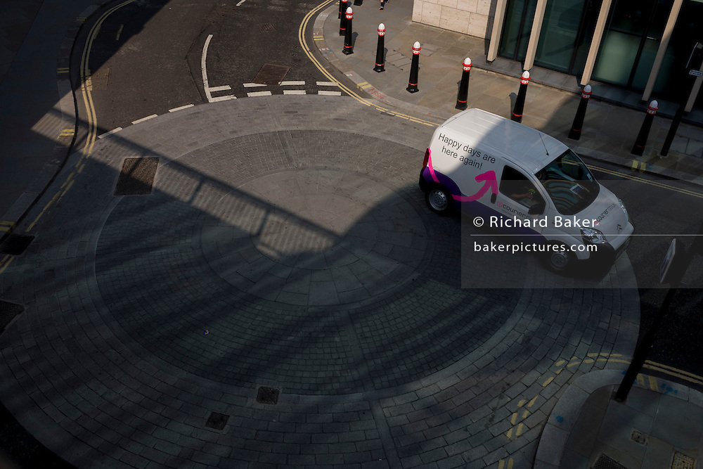 A white courier delivery van drives over a mini-roundabout in a City of London side street.