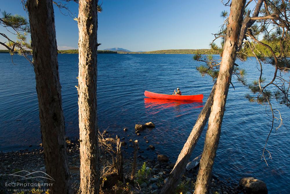 A man paddles his canoe on Seboeis Lake near Millinocket, Maine.  Mount Katahdin is in the distance. (MR)