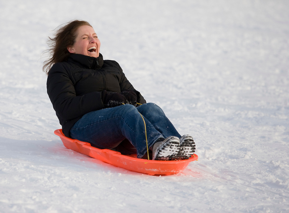 """(20110122, Boston, Massachusetts)..""""How do you steer this thing?"""" exclaims Jennifer Mehlrose, 37, of Denver, CO as she sleds in the Boston Common in Boston, Massachusetts on Saturday, January 22, 2011.  It was Mehlrose's first time sledding in decades, despite her snowy home...Photo by Brooks Canaday.."""