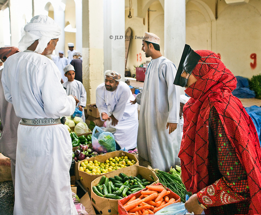 Market day in the Sinaw souk, Oman.  Livestock (goats, camels), vegetables, and weapons on offer.  Men and women shoppers.  Woman in red overdress wearing stiff black birka, buying vegetables.