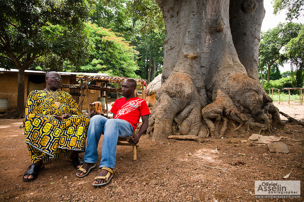 Kevin Kouassi Gallet and his father Hyacinthe Kouassi Koffi sit under a tree in Tano Akakro, Cote d'Ivoire on Saturday June 20, 2009.