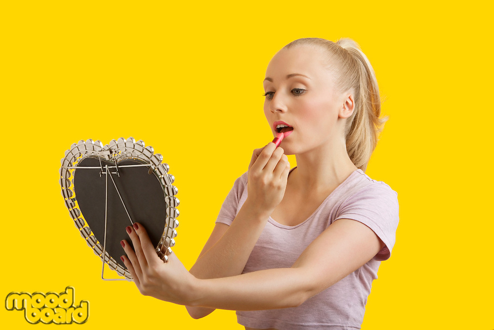 Beautiful young woman looking at mirror while applying lipstick over yellow background