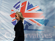 © Licensed to London News Pictures. 03/10/2011. MANCHESTER. UK. A woman walks past a hoarding carrying the Conservative Party logo at The Conservative Party Conference at Manchester Central today, October 3, 2011. Photo credit:  Stephen Simpson/LNP