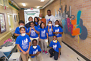 Montgomery ES students pose with Romero and Norris in front of their completed mural.