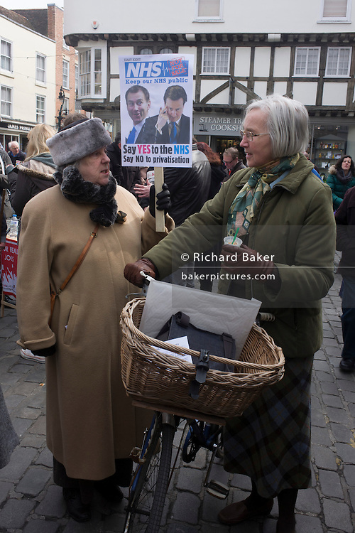 An elderly middle-class voters, discuss coalition plans over the NHS, holding a placard in Butter Market in the centre of Canterbury. Health Secretary Jeremy Hunt and David Cameron are parodied on the poster.