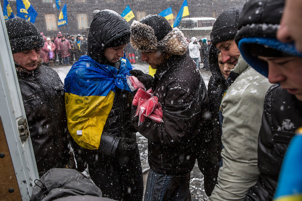 KIEV, UKRAINE - DECEMBER 6: Anti-government protesters distribute ponchos to ward off a heavy wet snow outside the Cabinet of Ministers on December 6, 2013 in Kiev, Ukraine. Thousands of people have been protesting against the government since a decision by Ukrainian president Viktor Yanukovych to suspend a trade and partnership agreement with the European Union in favor of incentives from Russia. (Photo by Brendan Hoffman/Getty Images) *** Local Caption ***