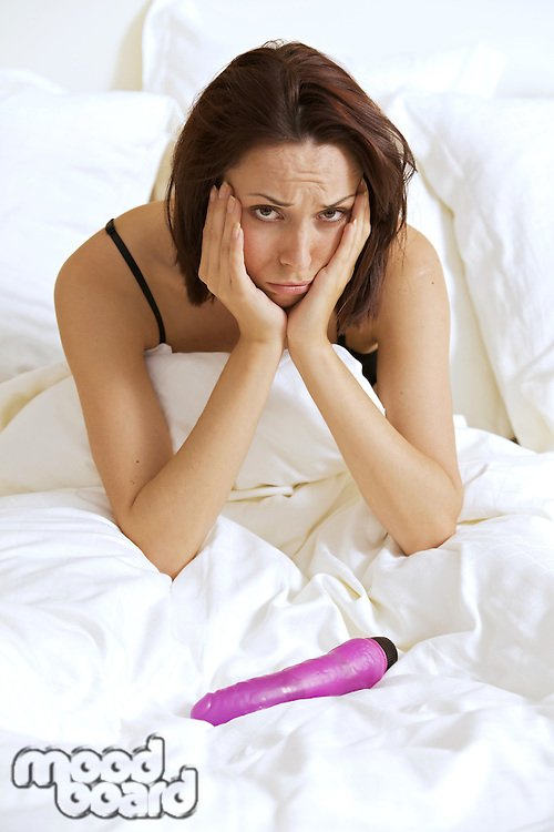 Portrait of young woman with hands on cheeks in front of dildo on bed