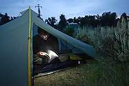"Andrew Hall winds down with a book on rock climbing in his tent at the Gros Ventre Campground on Thursday evening. From Virginia Beach, Virginia, Halll works three jobs and hopes to find a place so he can stay in the valley. ""I was passing through and then decided to come back,"" Hall said. ""It's a hole, you fall right back into it."""
