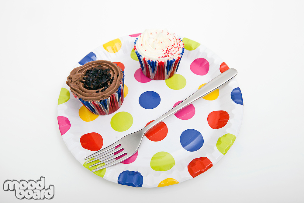 Cupcakes and fork in multicolored plate against white background