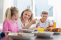 Happy family with children having breakfast at table