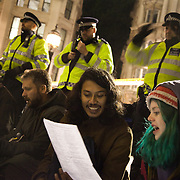 Peaceful singing in front of police lines.The London Stock Exchange was attempted occypied in solidarity with Occupy Wall in Street in New York and in protest againts the economic climate, blamed by many on the banks. Police managed to keep people away fro the Patornoster Sqaure and the Stcok Exchange and thousands of protestors stayid in St. Paul's Square, outside St Paul's Cathedral. Many camped getting ready to spend the night in the square.
