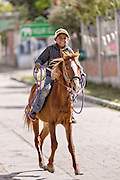 A young Mexican cowboy herds livestock down a village street by Mexican cowboys November 5, 2014 in Yaguar, Mexico.