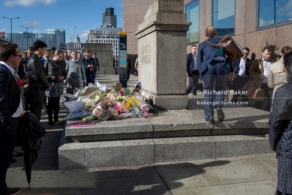 Three days after the terrorist attack in which 7 people died and many others suffered life-changing injuries on London Bridge and Borough Market, shrines of flower tributes grew at various locations around the police crime scene cordan on 6th June 2017, on London Bridge, in the south London borough of Southwark, England. City commuters now back at work walk respectfully and quietly past the floral memorial at the plinth marking the southern boundary of the City of London, the capital's financial district.
