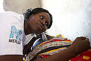 Irene Elim, a Merlin trained Midwife, listens to the baby's heart beat.Irene is working at he Kakimat outreach site. These clinics provide immunisations and nutrition support and advice.