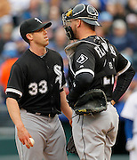 Chicago White Sox pitcher Dylan Axelrod (33) talks to Chicago White Sox catcher Tyler Flowers, right, after the Kansas City Royals scored two runs in the first inning off a Lorenszo Cain triple during a baseball game at Kauffman Stadium in Kansas City, Mo., Saturday, May 4, 2013.  (AP Photo/Colin E. Braley).