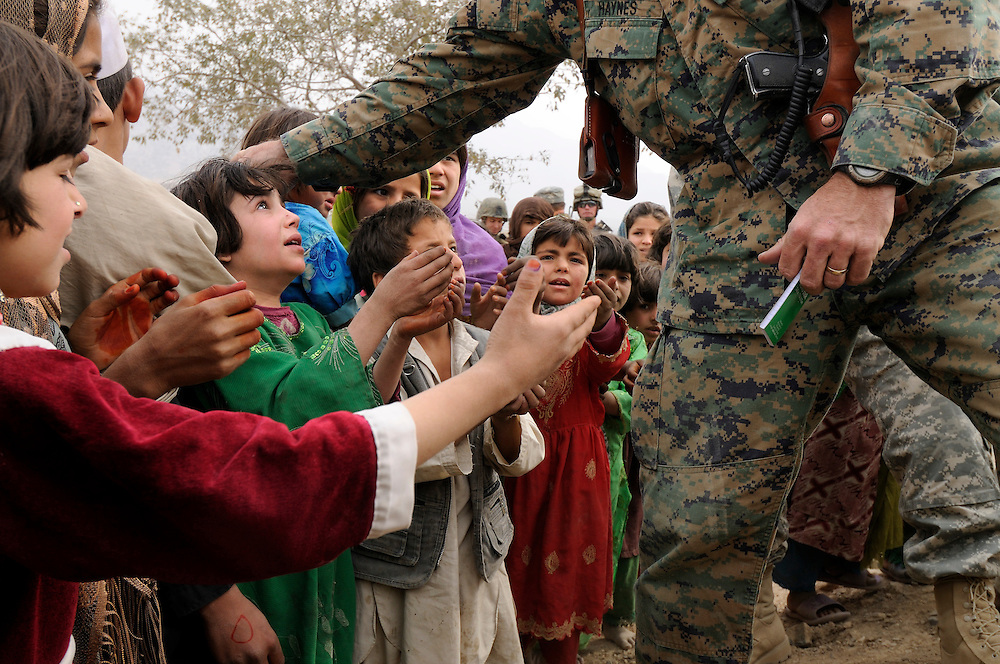 "US Marine Colonel Jeff Haynes, Commanding Officer, 201st Regional Corps Advisory Command, gives pens and note books to children in Tagab Valley during an operation.....To win a counterinsurgency, Haynes says you have to transform the environment and set conditions for change.  If people see there is hope, something worth them risking their lives for, then an army can win.  He says, ""You win them over, and they facilitate security pointing out the enemy. It is a symbiotic relationship.""  ...."