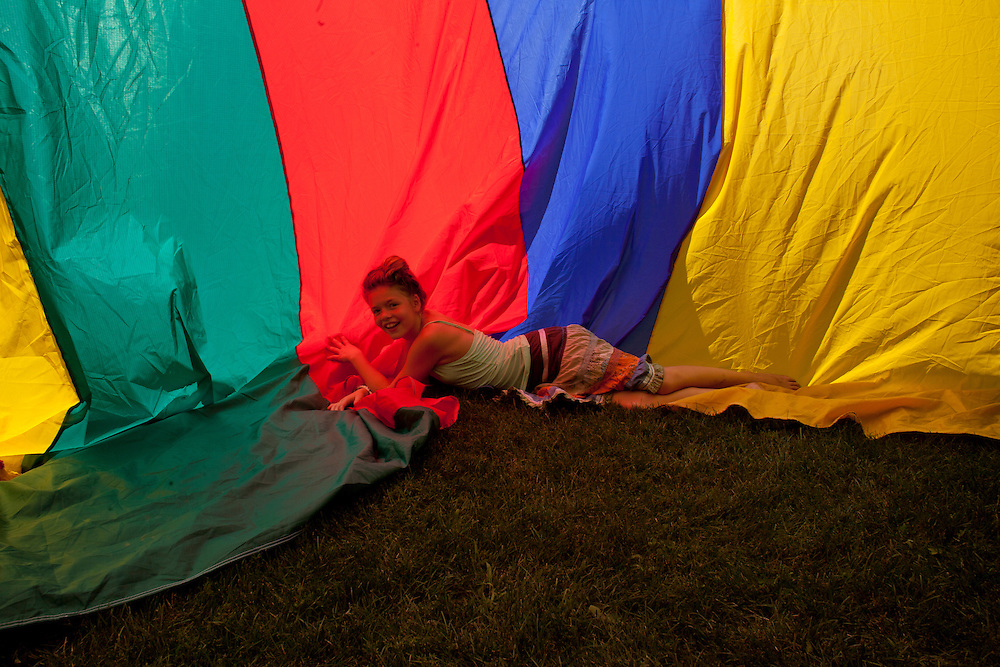Irish Stoll of Cedar Rapids plays in a giant parachute on the lawn at Camp Euforia on Friday, July 18, 2015. Jerry Hotz has hosted the annual music fest at his farm north of Lone Tree since 2003.