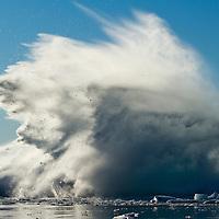 Greenland, Ilulissat, Slab of ice falling from massive iceberg calved from Jakobshavn Glacier sends up massive wave in Disko Bay on sunny summer evening