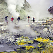 Tourists explore White Island on foot..Whakaari or White Island is an active volcano, situated 48 km from the east coast of the North Island of New Zealand, in the Bay of Plenty. .The island is roughly circular, about 2 km in diameter, and rises to a height of 321 m  above sea level. Sulphur mining was attempted but was abandoned in 1914 after ten workers were killed. It is New Zealand's only active marine volcano and perhaps the most accessible on earth, attracting scientists and volcanologists worldwide as well as many tourists. It is part of the Taupo Volcanic Zone.. The main activities on the island now are guided tours and scientific research. White Island, New Zealand,. 5th December 2010.  Photo Tim Clayton..
