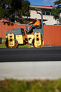 road roller operated by a road worker to compact or flatten new tarmac for road paving at browns bay, auckland, new zealand